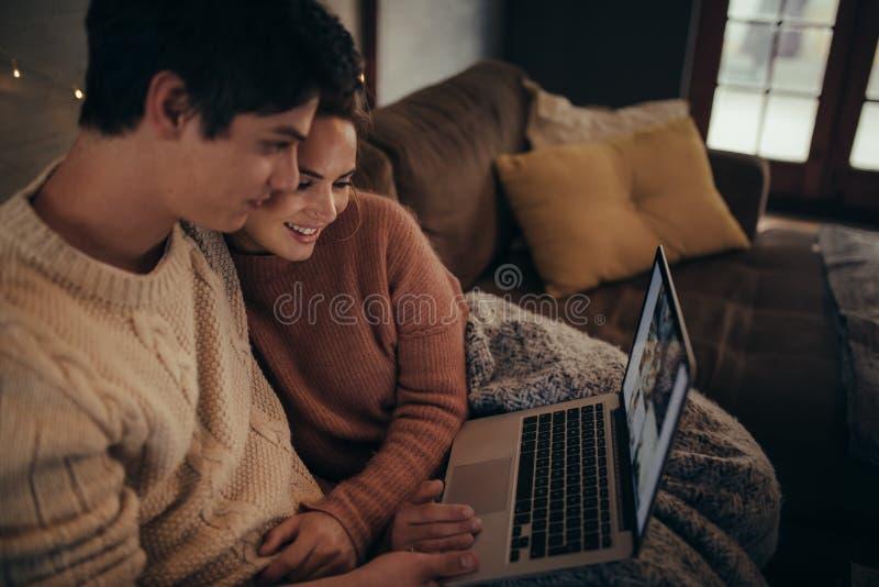 Пары используя компьтер-книжку в доме hygge стоковая фотография