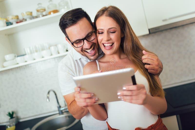 Пары используя цифровой планшет в кухне стоковые изображения