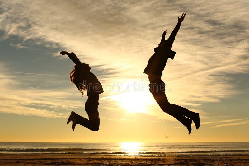 Пары или друзья скача на пляж на заходе солнца стоковое изображение rf