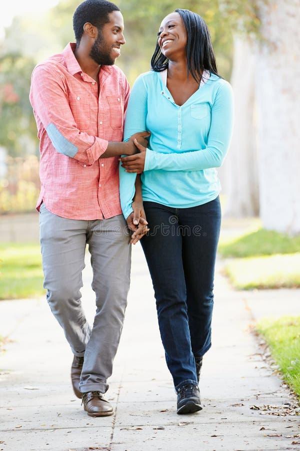 Пары идя вдоль пригородной улицы совместно стоковое фото