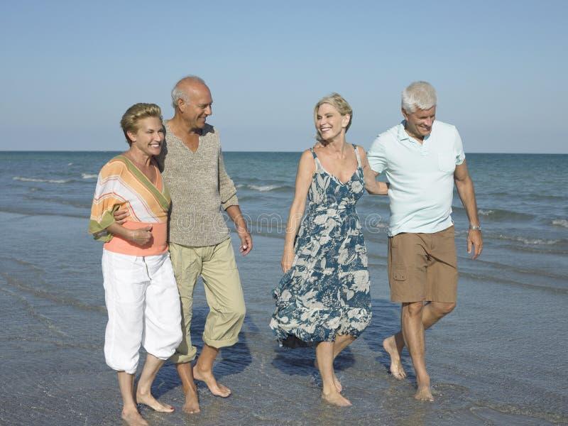 Пары идя совместно на тропический пляж стоковые изображения