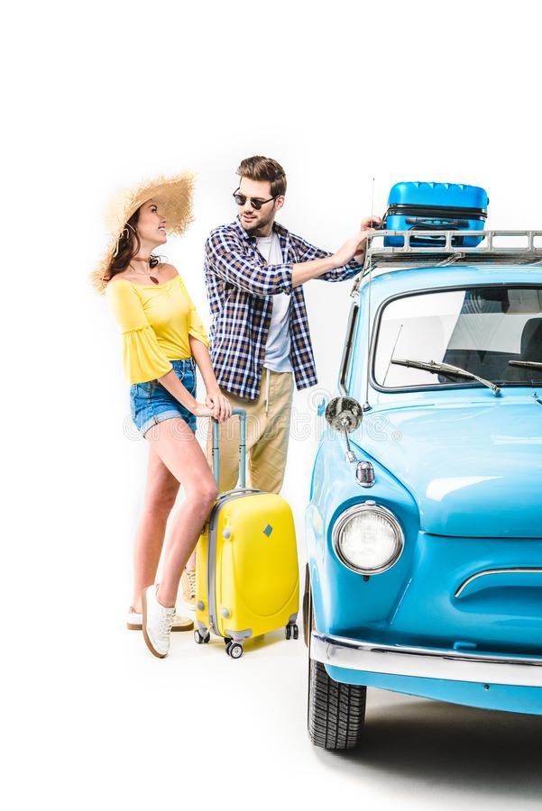Пары кладя багаж на крышу автомобиля стоковая фотография