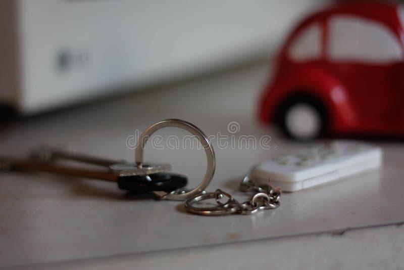 Пары ключей с ключевым кольцом на таблице на предпосылке красного автомобиля стоковые изображения rf