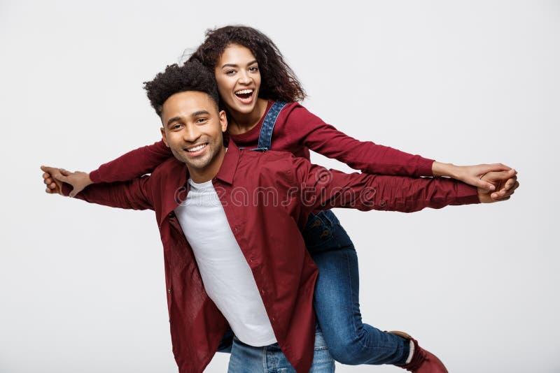 Пары конца-вверх молодые Афро-американские ехать назад и играя как самолет стоковые фотографии rf