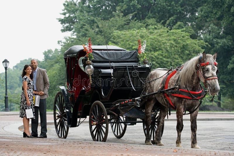 Пары, который стоят рядом с экипажом нарисованным лошадью стоковое фото