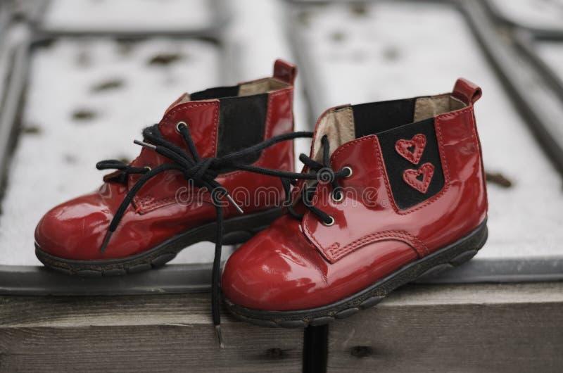 Пары красных ботинок младенца с 2 сердцами для newborn, который нужно нести Подарок на день ` s валентинки St стоковые фото