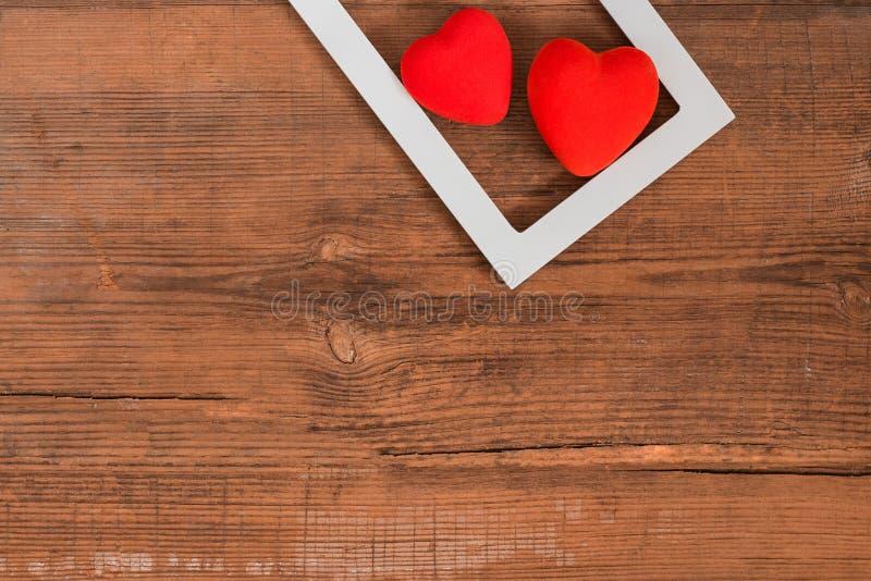 Пары красных сердец в белой рамке на винтажном деревянном столе, взгляде сверху предпосылка дня валентинок Святого стоковые фотографии rf