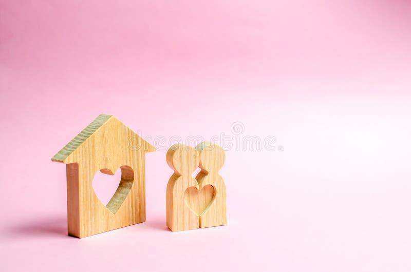 Пары любовников стоят около людей дома с сердцем Счастливая семья около нового дома Концепция обнаружения гнезда любов стоковая фотография rf
