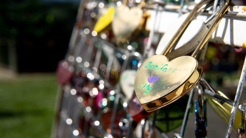 Пары любов запирают висеть на рельсе стоковое фото
