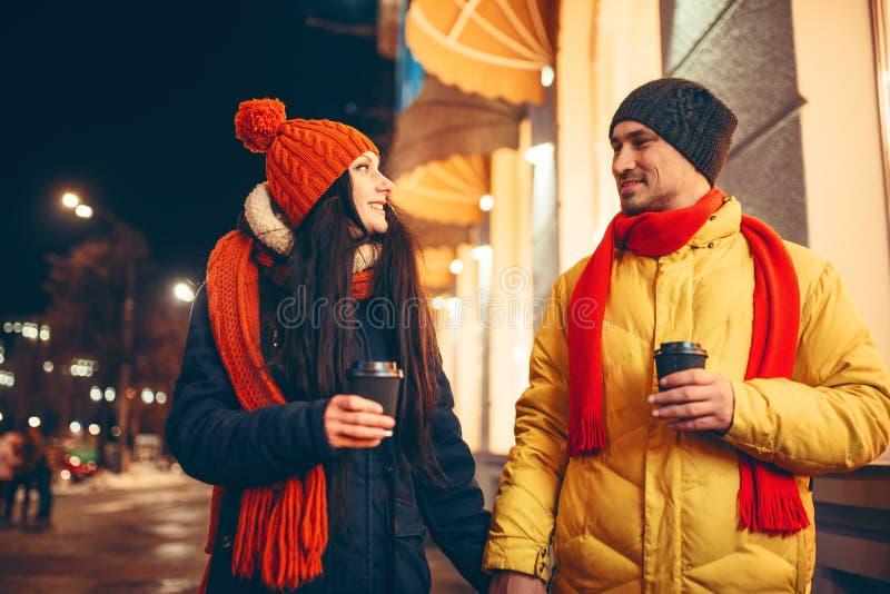 Пары любов с кофе идя вниз по улице стоковые изображения
