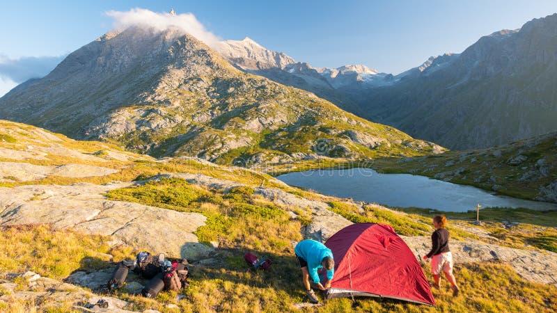 Пары людей настраивая располагаясь лагерем шатер на горах, промежуток времени Лето рискует на Альпах, идилличном озере и саммите стоковое изображение rf