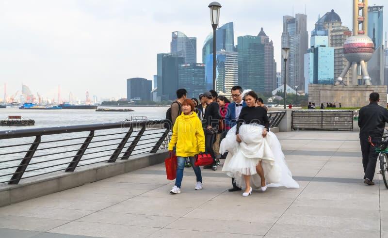 Пары молодого  Ñ hinese в платье свадьбы идя вдоль прогулки на бунде стоковые изображения