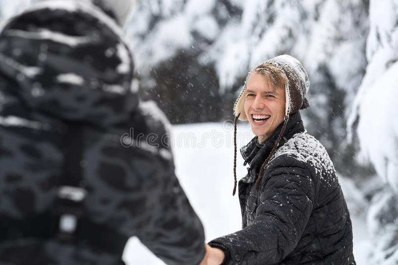 Пары молодого человека идя в парней леса снега внешние держа руки стоковые изображения