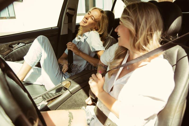 Пары молодой лесбиянки подготавливая для отключения каникул на автомобиле в солнечном дне стоковые изображения