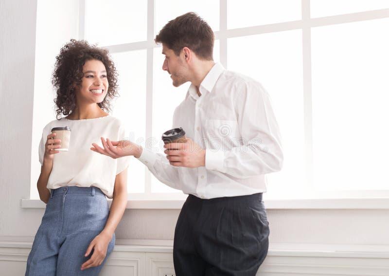 Пары молодых коллег выпивая кофе около окна стоковые фотографии rf