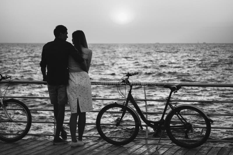 Пары молодых любовников битника обнимая на пляже, смотря один другого во время восхода солнца на деревянном временени палубы стоковые изображения