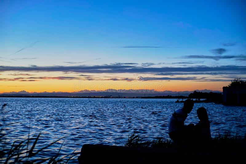 Пары молодых людей предусматривают заход солнца в Albufera Валенсия стоковое фото rf