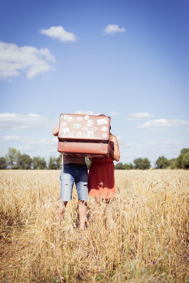 Пары, мужчина и женщина с сюит-случаем, предпосылкой голубого неба outdoors стоковые фото