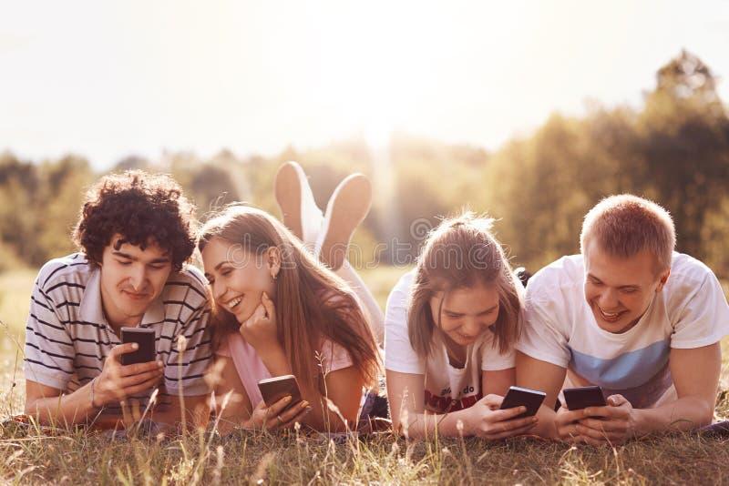 2 пары наблюдают что-то в их умных телефонах, используют интернет для загружать музыку или видео watchng, имеет довольные выражен стоковое изображение rf