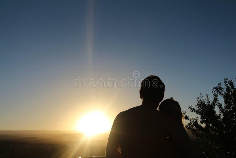 Пары наблюдая заход солнца стоковая фотография
