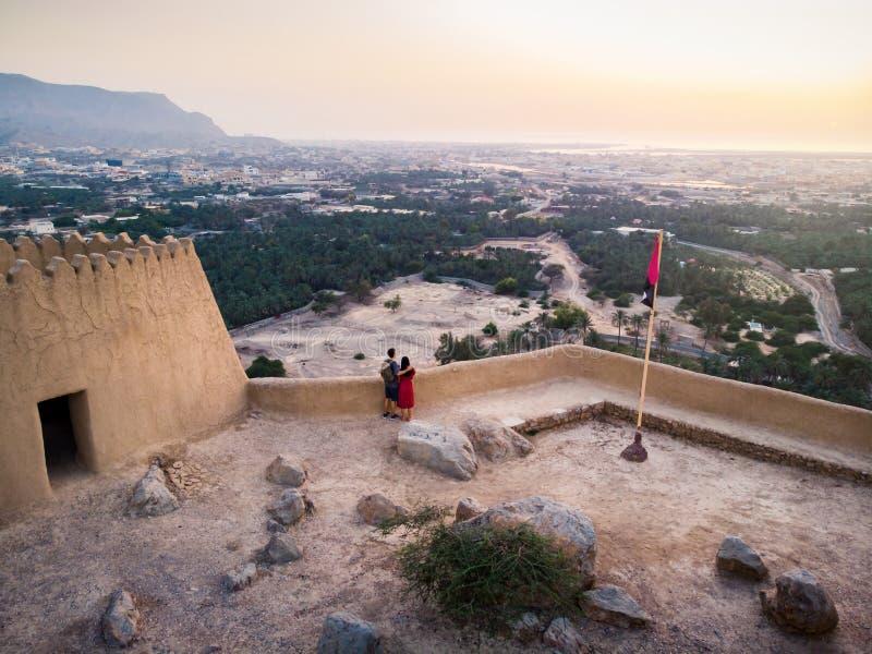 Пары наслаждаясь взглядом захода солнца от форта Dhayah в ОАЭ стоковые изображения rf