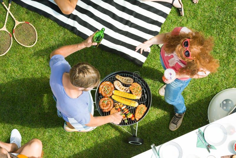 Пары наслаждаясь приём гостей в саду барбекю стоковое изображение