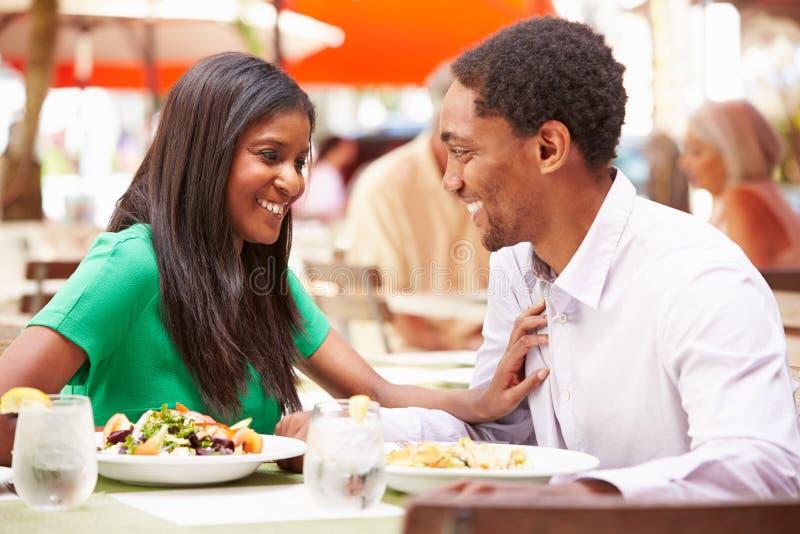 Пары наслаждаясь обедом в внешнем ресторане стоковое фото