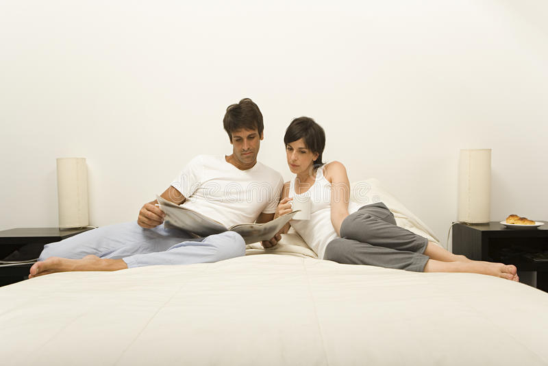 Пары на газете чтения кровати стоковая фотография