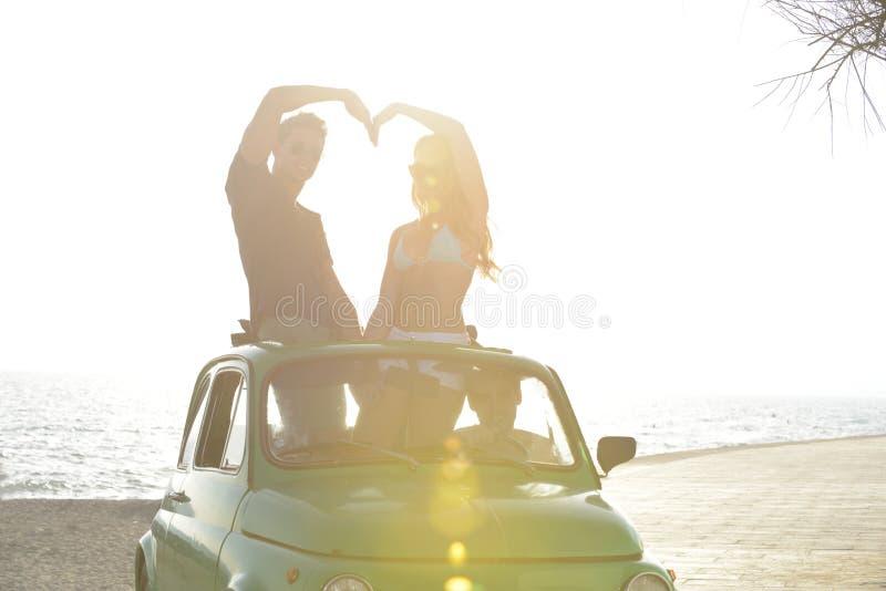 Пары на заходе солнца на пляже с автомобилем стоковые изображения rf