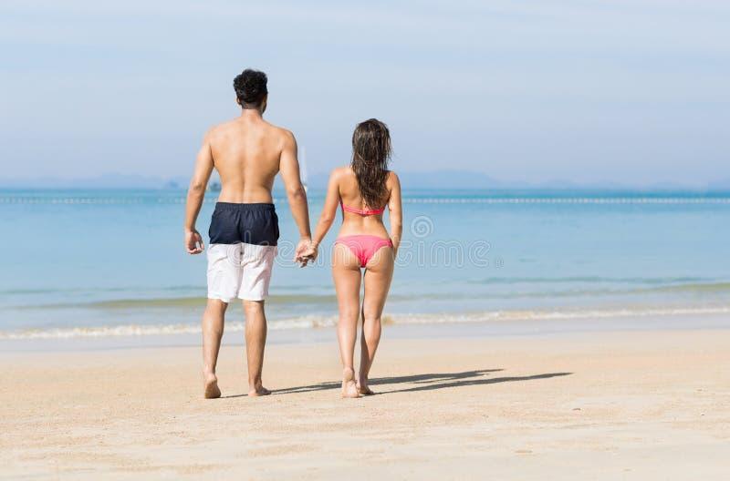 Пары на летних каникулах пляжа, молодые люди в влюбленности идя, женщина человека держа океан моря рук стоковое фото