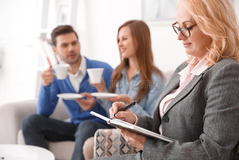Пары на офисе по сбыту недвижимости при агент принимая примечания в плановике стоковая фотография rf