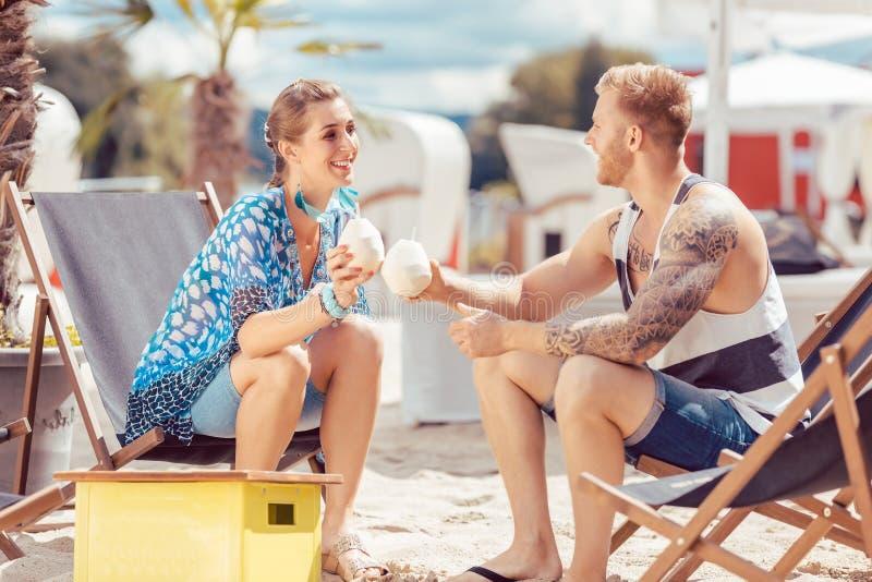 Пары на пляже имея воду кокоса стоковые изображения rf