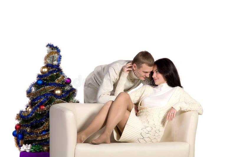 Пары на рождественской елке рядом с белой софой стоковые фотографии rf