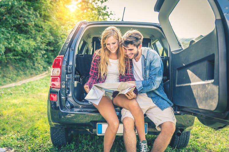 Пары на с автомобиле дороги смотря карту стоковые фотографии rf