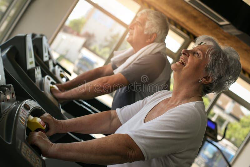 Пары на jogging машине Старшая разминка пар в g стоковые фотографии rf