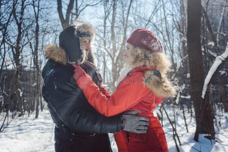 Пары обнимая находящся в любов на холодный зимний день в снеге стоковые изображения