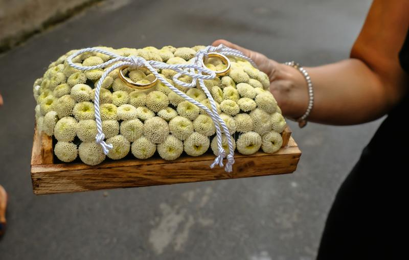 Пары обручальных колец золота аранжировали на кровати сметанообразных цветков стоковая фотография