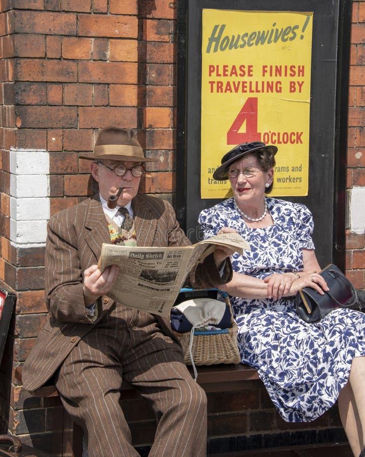 Пары одели в одежде военного времени, ожидании на станции, во время стоковые фото