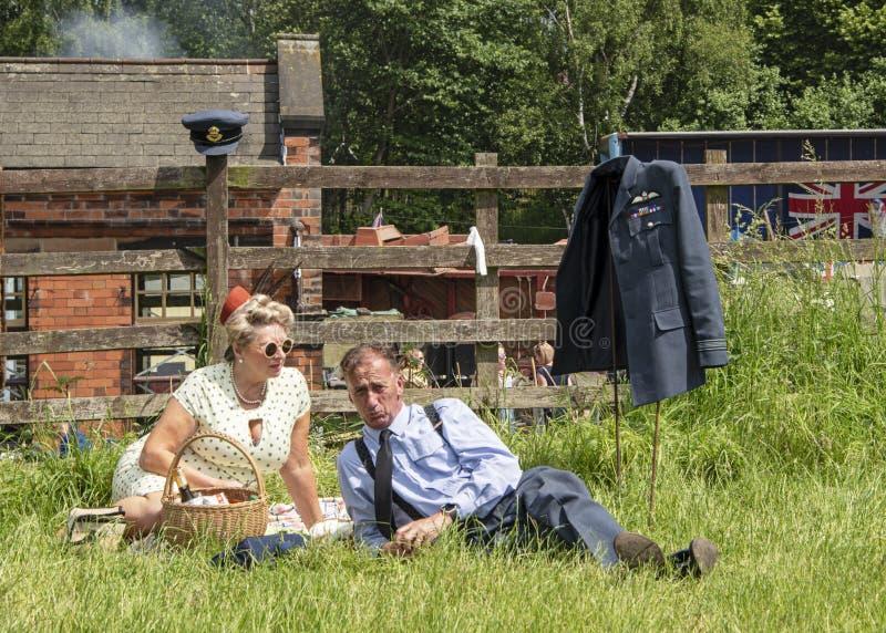 Пары одетые в одежде военного времени, наслаждаются пикником, во время Victo стоковые фотографии rf