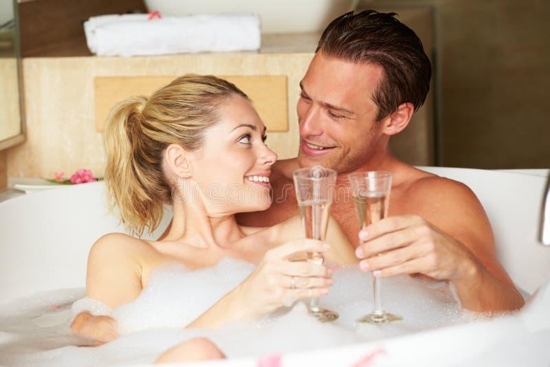 Пары ослабляя в ванне выпивая Шампань совместно стоковая фотография
