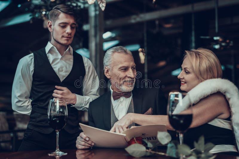 Пары отдыхая в ресторане и женщине сделали выбор стоковые изображения