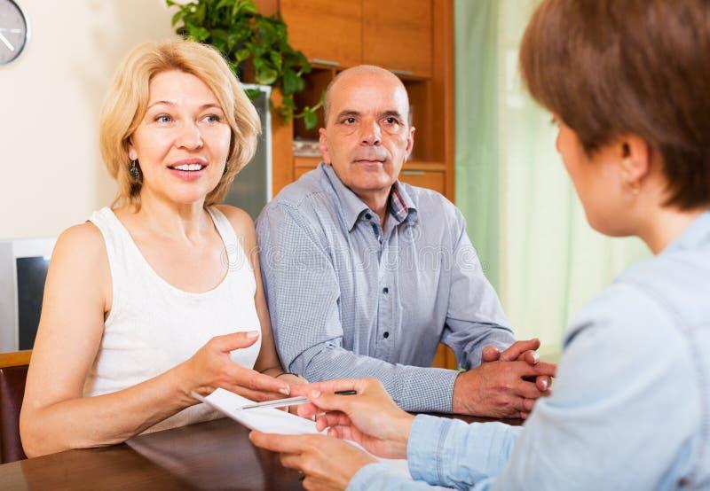 Пары пенсионеров разговаривая с менеджером стоковое изображение