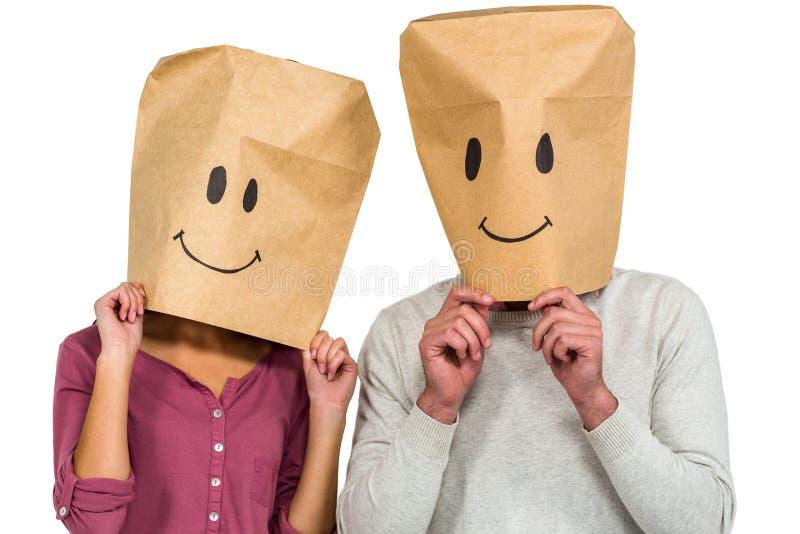 Пары покрывая их стороны с бумажной сумкой стоковая фотография