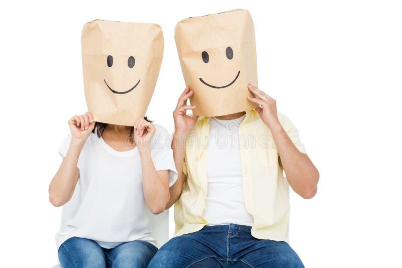 Пары покрывая их стороны с бумажной сумкой стоковые фото