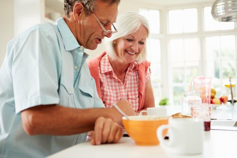Пары постаретые серединой смотря таблетку цифров над завтраком стоковое фото rf