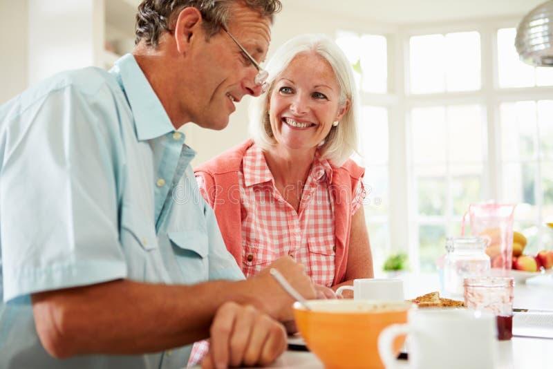 Пары постаретые серединой смотря таблетку цифров над завтраком стоковые фото