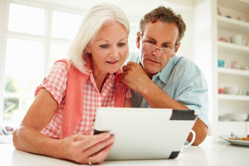 Пары постаретые серединой смотря таблетку цифров стоковые изображения
