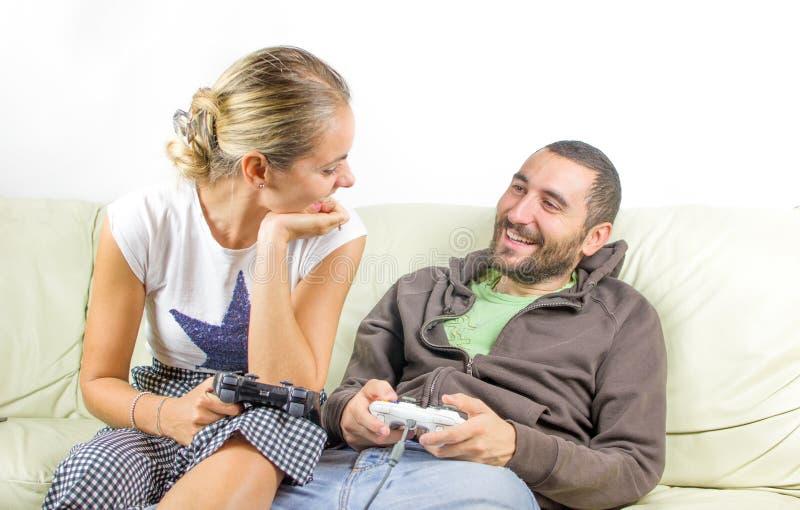 Пары потехи смотрят один другого - сыграйте видеоигры стоковая фотография rf