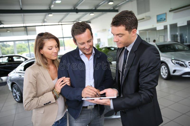 Пары подписывая контракт приобретения на таблетке стоковое изображение rf