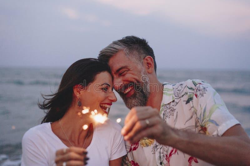 Пары празднуя с бенгальскими огнями на пляже стоковые фотографии rf